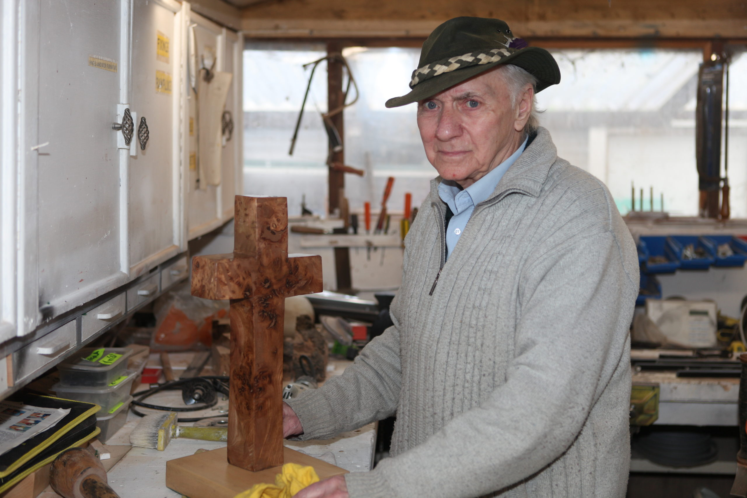 Brian crafting a wooden cross in his workshop
